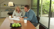 Wide, track shot of male and female at dinning table looking at personal fina Stock Footage
