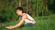 Teenagers with laptop resting on meadow. Stock Footage