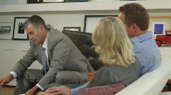 Wide shot off couple on sofa signing contract with financial advisor Stock Footage