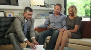 Wide shot off couple on sofa signing contract and handshake financial advisor Stock Footage