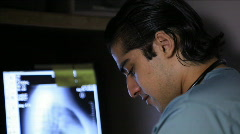 rack focus tilt doctor looking at x-ray - stock footage