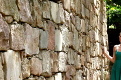 Sad woman walking by the stone wall Stock Footage