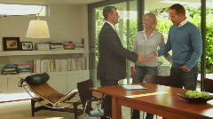 Wide shot off couple handshake with sales person in contemporary home Stock Footage