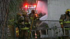 Firefighters working a house fire Stock Footage