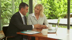 Wide, shot off female at dinning table with financial advisor showing documen Stock Footage