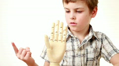 Boy flexes fingers of wooden model of human hand Stock Footage