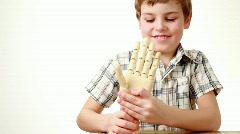 Boy flexes wrist of wooden model of human hand Stock Footage
