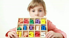 Girl holds a box with cells and looks at wooden figures in it Stock Footage