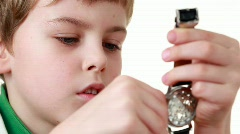 boy starts a wristlet watch on white - stock footage