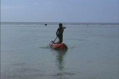 Rarotonga Boy paddling boat Stock Footage