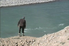 Men throwing rocks in the Indus River in Ladakh Stock Footage
