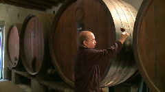 Stock Video Footage of Winemaker sniffs wine in ancient cellar sepia wide