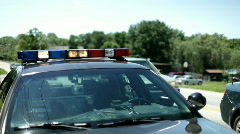 Police Car sitting on Road with Lights Flashing Stock Footage