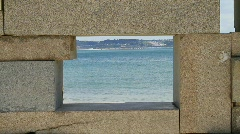 Roller-Skater Passing by the Beach, framed in a Very Small Stone Window Stock Footage