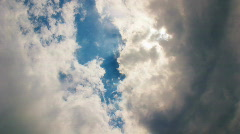 Clouds flying on blue sky dramatically with sun rays Stock Footage
