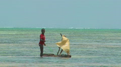 Boys make a crude sailboat in the ocean on a tropical island. Stock Footage