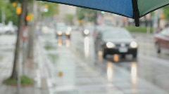 Umbrella with rainy defocused street. - stock footage