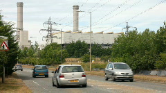 Cars passing a natural gas fired electricity power station England UK Stock Footage