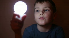 Boy in blue T-shirt switchs on and off a light bulb Stock Footage