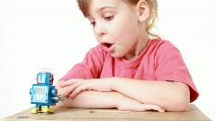 Girl is watching going forward clockwork robot Stock Footage