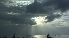 Sun Setting through dramatic clouds with Fishermen's boats seen in the Stock Footage