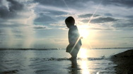 Stock Video Footage of Toddler Playing In Beach Water At Sunset