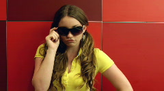 Girl posing with Sunglasses on red squares - stock footage