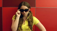 Stock Video Footage of Girl posing with Sunglasses on red squares