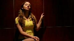 Girl sitting under Dramatic light Stock Footage