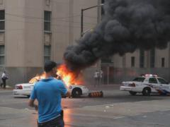 G20 Toronto. Reporter and Burning police car. SD. Stock Footage