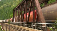 Railroad, freight train over bridge, mountains, medium long Stock Footage