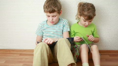 Boy and girl sit on floor leaning against wall and read Stock Footage