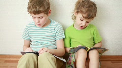 boy and girl sit on floor leaning against wall and read books - stock footage