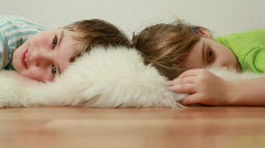 Boy and girl lie on floor on shawl and are kept in hands Stock Footage