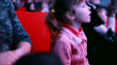 Impressionable girl sits on a red chair in auditorium of circus - stock footage