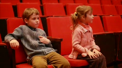 Impressionable girl and boy sits on chair in empty auditorium of circus - stock footage