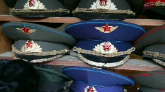 Many souvenir military caps with Soviet and Russian symbols in shop Stock Footage