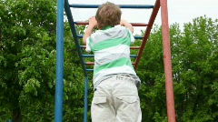 Boy in shirt climbs down wall bars like monkey on playground Stock Footage