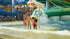 Charming woman , man and children fool near fountain in pool in water park Stock Footage