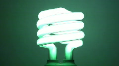Green Colored Energy Saving Lightbulb Being Turned On - stock footage