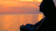Woman watching sunset Stock Footage