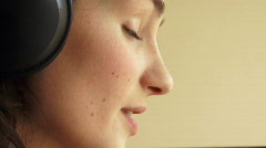 Happy girls face in ear-phones Stock Footage