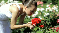 Young attractive woman smelling red roses in garden Stock Footage