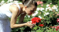Stock Video Footage of Young attractive woman smelling red roses in garden