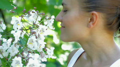 Young beautiful woman smelling flowers an flirting with camera Stock Footage