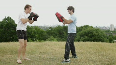 Two male box training in park - stock footage