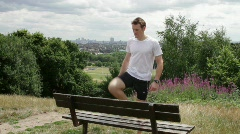 Male stretching on bench in park Stock Footage