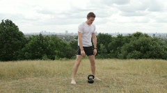 Male exercising with cow bell in park Stock Footage
