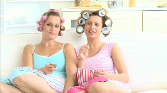 Relaxed women eating popcorn wearing hair rollers Stock Footage