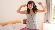 Female dancing in bed with headphones Stock Footage